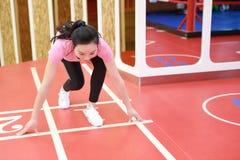 Femme de sourire chinoise de personnes d'Asain prête pour courir dans le gymnase Sports, puissance photo libre de droits
