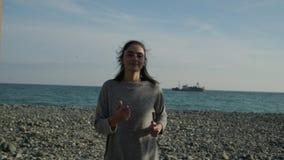 Femme de sourire courant sur la plage banque de vidéos