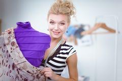 Femme de sourire de couturier tenant le mannequin proche dans le bureau Photographie stock libre de droits