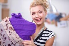 Femme de sourire de couturier tenant le mannequin proche dans le bureau Image stock