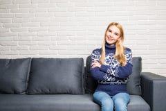 Femme de sourire détendant sur le sofa à la maison tout en regardant l'appareil-photo et le sourire Photographie stock libre de droits