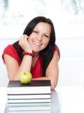 Femme de sourire d'étudiant avec des livres et l'APPL Photo stock