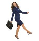 Femme de sourire d'affaires avec la serviette allant gaiement en longueur Photographie stock