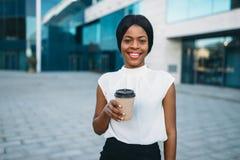 Femme de sourire d'affaires avec la tasse de café de carton photos stock