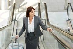 Femme de sourire d'affaires avec la valise se tenant sur l'escalator Image libre de droits