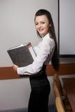 Femme de sourire d'affaires dans le bureau avec des documents Photo libre de droits