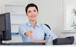 Femme de sourire d'affaires donnant sa main Images stock