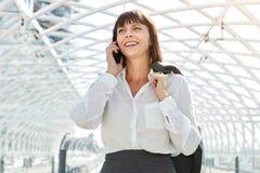 Femme de sourire d'affaires parlant au téléphone intelligent dans le terminal Photos stock