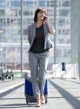 Femme de sourire d'affaires parlant au téléphone portable à l'aéroport Photo libre de droits
