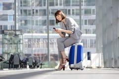 Femme de sourire d'affaires regardant le téléphone portable Images stock