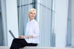 Femme de sourire d'affaires s'asseyant dehors avec l'ordinateur portable photographie stock