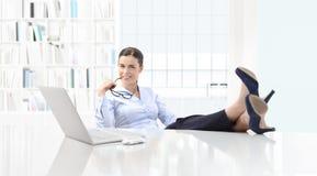 Femme de sourire d'affaires satisfaisantes dans le bureau avec l'ordinateur et les honoraires Image stock