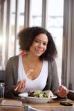 Femme de sourire d'afro-américain dans le restaurant mangeant de la salade Images stock