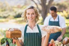 Femme de sourire d'agriculteur tenant des pains Photographie stock libre de droits