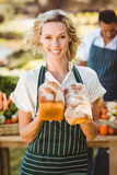 Femme de sourire d'agriculteur tenant des pains Images stock