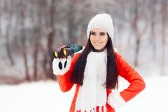 Femme de sourire d'hiver avec des jumelles recherchant Noël Images stock