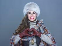 Femme de sourire d'isolement sur le bleu froid montrant les mains en forme de coeur Images stock