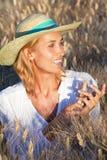 Femme de sourire dans des domaines de blé photographie stock libre de droits