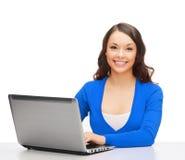 Femme de sourire dans des vêtements bleus avec l'ordinateur portable Photographie stock libre de droits