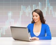 Femme de sourire dans des vêtements bleus avec l'ordinateur portable Images stock