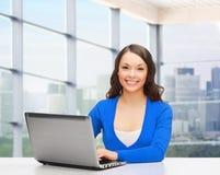 Femme de sourire dans des vêtements bleus avec l'ordinateur portable Images libres de droits