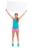 Femme de sourire dans des vêtements vibrants tenant la bannière vide au-dessus de la tête Image libre de droits