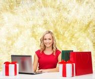Femme de sourire dans la chemise rouge avec les cadeaux et l'ordinateur portable Photo libre de droits
