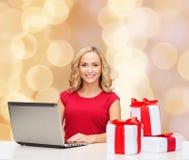 Femme de sourire dans la chemise rouge avec les cadeaux et l'ordinateur portable Image libre de droits