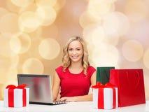 Femme de sourire dans la chemise rouge avec les cadeaux et l'ordinateur portable Photos libres de droits