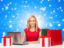 Femme de sourire dans la chemise rouge avec les cadeaux et l'ordinateur portable Image stock