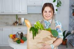 Femme de sourire dans la cuisine avec un sac des achats d'épiceries image libre de droits