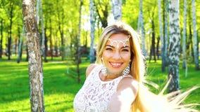 Femme de sourire dans la danse sensuelle de costume dans le verger de bouleau avec l'effet de fusée de lentille banque de vidéos