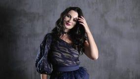 Femme de sourire dans la robe chic et avec le maquillage se tenant sur le mur de gris de fond banque de vidéos