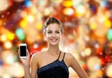 Femme de sourire dans la robe de soirée avec le smartphone Image libre de droits