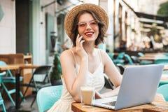 Femme de sourire dans la robe et le chapeau de paille parlant par le smartphone photographie stock
