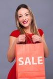 Femme de sourire dans la robe rouge avec des paniers Photos stock