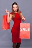 Femme de sourire dans la robe rouge avec des paniers Photographie stock
