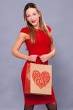 Femme de sourire dans la robe rouge avec des paniers Image stock