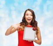Femme de sourire dans la robe rouge avec le PC de comprimé Photo libre de droits