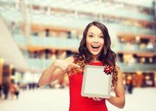 Femme de sourire dans la robe rouge avec le PC de comprimé Photo stock