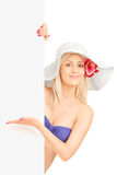 Femme de sourire dans le bikini se tenant et faisant des gestes sur un panneau Images libres de droits