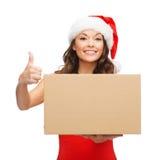 Femme de sourire dans le chapeau d'aide de Santa avec la boîte de colis photos stock
