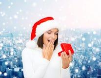 Femme de sourire dans le chapeau d'aide de Santa avec le boîte-cadeau Image stock