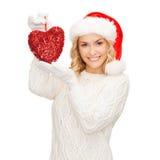 Femme de sourire dans le chapeau d'aide de Santa avec le coeur rouge Photo libre de droits