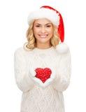 Femme de sourire dans le chapeau d'aide de Santa avec le coeur rouge Image stock
