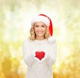 Femme de sourire dans le chapeau d'aide de Santa avec le coeur rouge Image libre de droits