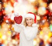 Femme de sourire dans le chapeau d'aide de Santa avec le coeur rouge Photo stock
