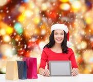 Femme de sourire dans le chapeau d'aide de Santa avec le PC de comprimé Images libres de droits