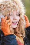 Femme de sourire dans le chapeau de fourrure parlant au téléphone portable Photos stock
