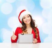 Femme de sourire dans le chapeau de Santa avec le PC de cadeau et de comprimé Image stock